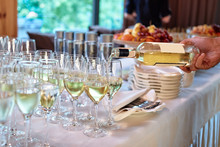 Waiter Pours Wine Into Wineglass At Wedding Reception, Copy Space. Sparkling Glassware With Wine And Champagne On Dinner Table In Restaurant