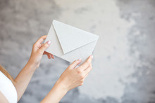 Close-up Girl Holds With Two Hands A White Envelope Wedding Invitation Notice On A Gray Background.