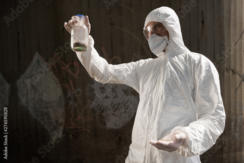 ecologist in protective costume and respirator holding bottle with soil sample Canvas-taulu