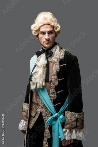 handsome victorian gentleman in wig standing isolated on grey Canvas Print