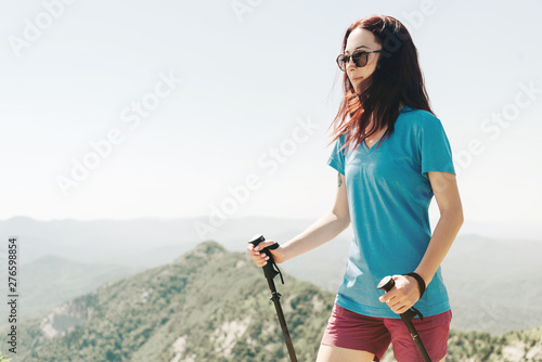 Sporty woman walking with trekking poles in summer mountains.