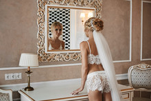 Beautiful And Sexy Blonde Model Woman With A Perfect Slim Body, In Fashionable Lace Lingerie And In The Veil, Looking In The Mirror On Her Reflexion At Vintage Luxury Interior
