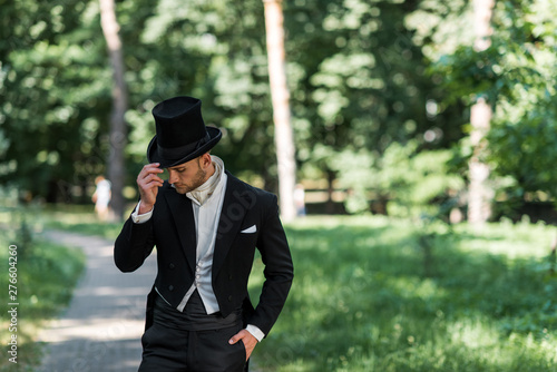 Obraz handsome young victorian man touching hat and standing with hand in pocket outside - fototapety do salonu