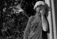 Mujer Con Mano En La Cara Con Escena De Virgen Y Cristo En Brazos Al Fondo. Blanco Y Negro