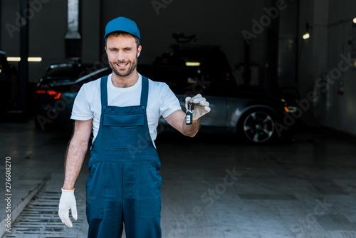 Fototapeta handsome bearded car mechanic holding keys in car service obraz