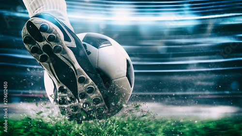 Football scene at night match with close up of a soccer shoe hitting the ball wi Canvas Print