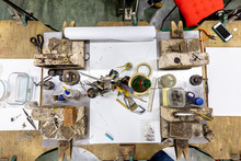Top Down View On A Wooden Work Bench Equipped With Tools For The Making Of Jewellery And Metal Processing With Different Inflammable Surfaces And Heating Stations