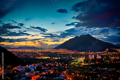 Foto op Aluminium Groen blauw city at night below the mointains