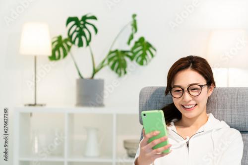 Photo 部屋でスマホを見る女性