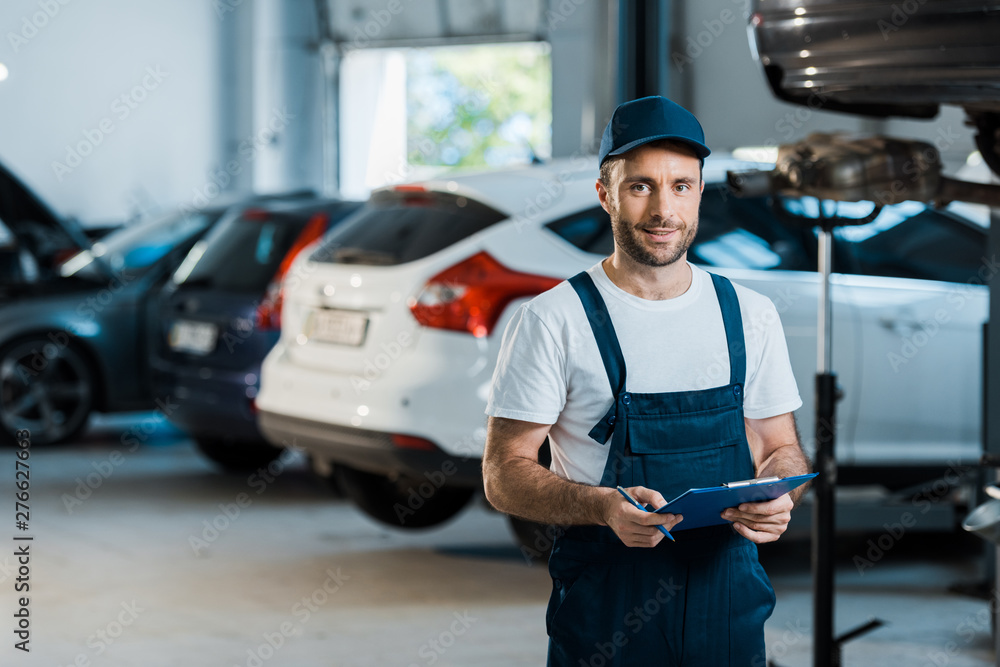 Fototapety, obrazy: happy bearded car mechanic looking at camera and holding clipboard near cars