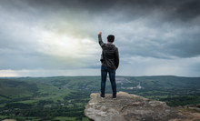 A Man Standing On The Edge Of Cliff And Showing His Fist To The Sky As Symbol Of Success And Victory.