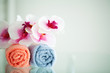 Colored towels and orchid on white table with copy space on bath room background
