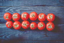 Two Rows Of Freshly Picked Tomatoes On Dark Rustic Wooden Background