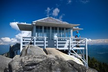Man Standing By  Fire Lookout Hut On Mountain Top With Expansive View. Hiking In Mount Pilchuck State Park Near Seattle. Everett. WA. United States Of America