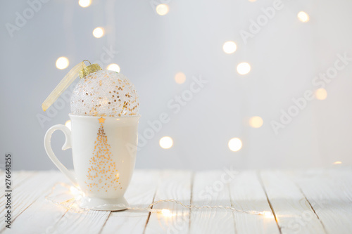 Valokuvatapetti Christmas ball in white cup on wooden table on background Christmas lights