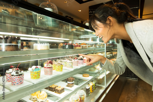 Many Good Looking design and colorful Bakery Cake in refrigerator windows show, present variety of Price and vanilla chocolate birthday cake for special occasion, selected by skinny asian woman dress