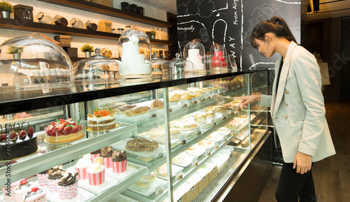 Photo sur Aluminium Boulangerie Many Good Looking design and colorful Bakery Cake in refrigerator windows show, present variety of Price and vanilla chocolate birthday cake for special occasion, selected by skinny asian woman dress