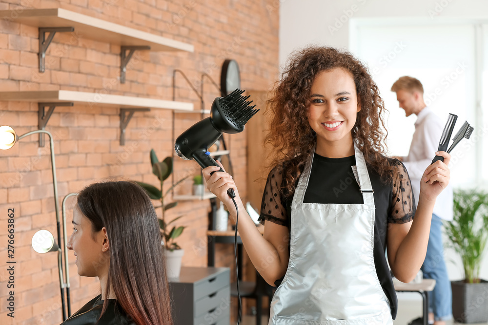 Fototapeta Young African-American hairdresser in beauty salon