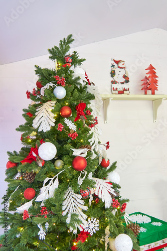 Christmas Tree Bows White.Christmas Tree Decorated With Balls And Bows Near White Wall