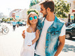 Smiling beautiful girl and her handsome boyfriend walking in the street. Woman in casual summer dress and man in jeans clothes. Happy cheerful couple family having fun in sunglasses