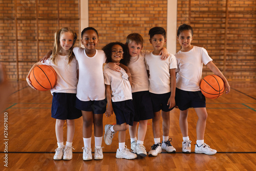 Front view of schoolkids standing and looking at camera at basketball court