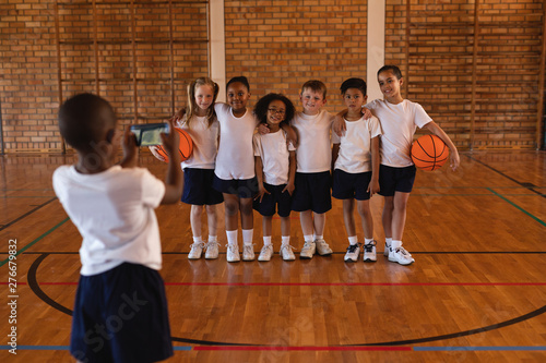 Rear view of schoolboy clicking photo with mobile phone of his friends at basketball court
