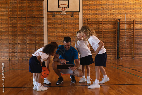 Schoolkids looking at clipboard at basketball court in school