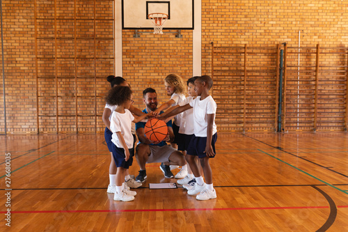 Schoolkids and basketball coach forming hand stack at basketball court in school
