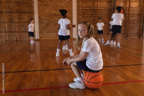Side view of schoolgirl sitting on basketball and looking at camera at basketball court