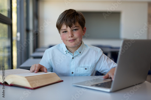 Schoolboy reading a book and using laptop in a classroom