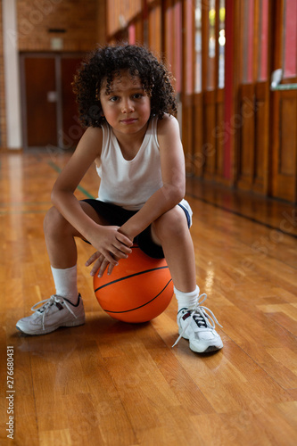 Schoolboy sitting on basketball and looking at camera in basketball court