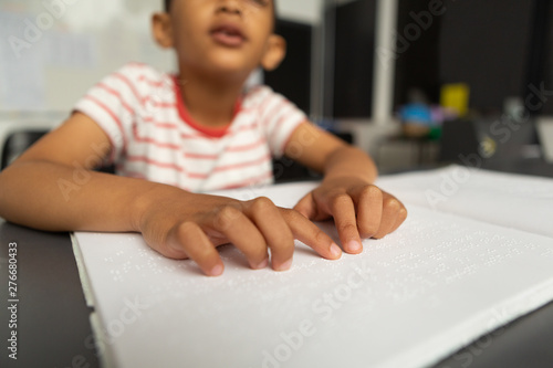 Blind schoolboy hands reading a braille book in classroom