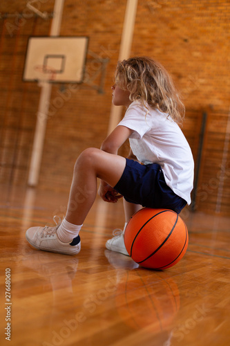Schoolgirl sitting on basketball on basketball court