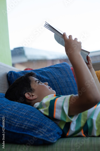 Schoolboy lying on sofa and reading a book in library