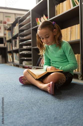 Schoolgirl sitting on floor in cross-legged position and reading a book in library