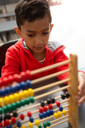 Schoolboy learning math with abacus at desk in a classroom - 276680805