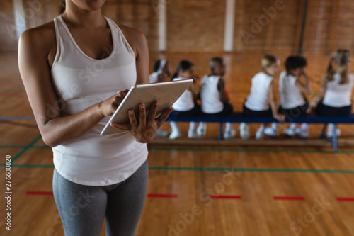 Mid section female basketball coach using digital tablet at basketball court