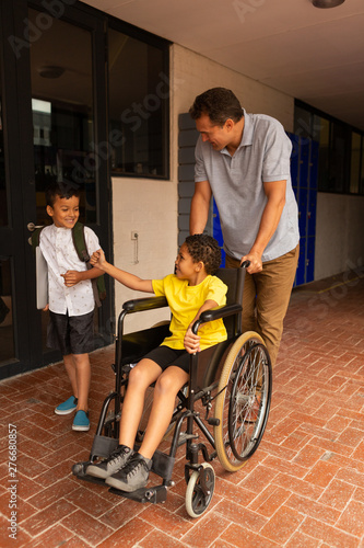 Schoolboy in wheelchair with male teacher and classmate in the corridor