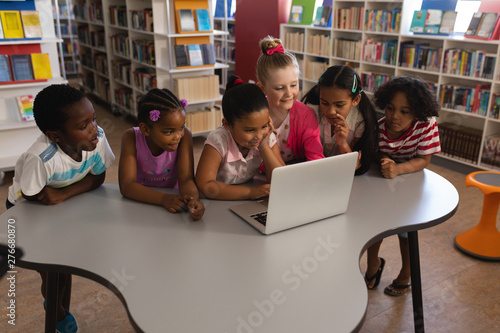 Schoolkids studying together on laptop at table in school library