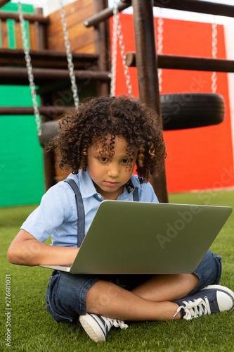 Schoolgirl using laptop in the school playground