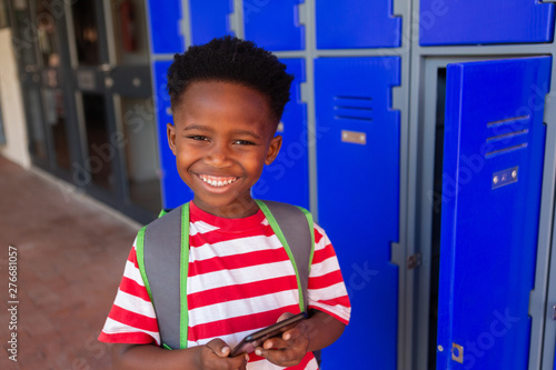 Schoolboy holding mobile phone in the locker room