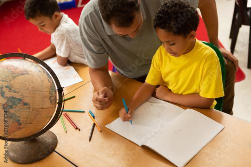 Male teacher teaching a schoolboy in a classroom