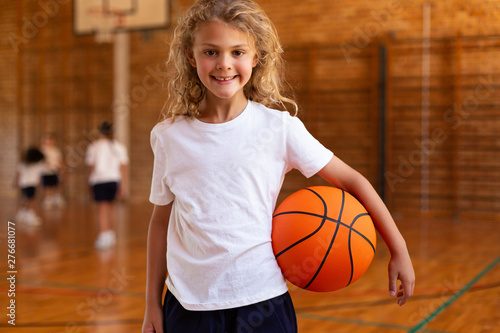 Schoolgirl with basketball looking at camera in basketball court