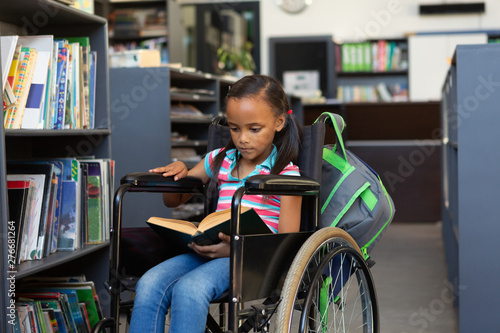 Disabled schoolgirl reading a book in the library