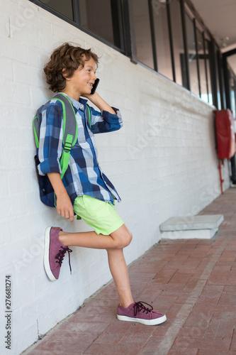 Schoolboy talking on mobile phone in the corridor