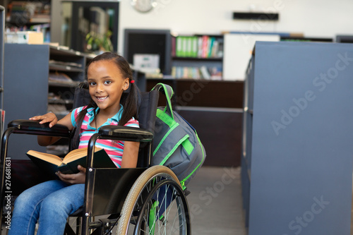 Disabled schoolgirl reading a book in the classroom