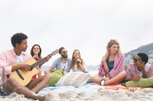 Man playing guitar while friends enjoying on beach