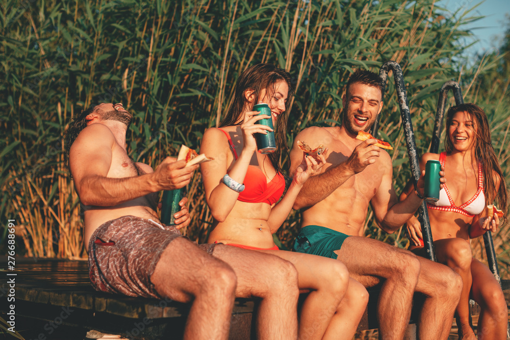 Fototapety, obrazy: Group of young people eats pizza and drinking beer on a dock by the river during the summer sunny day