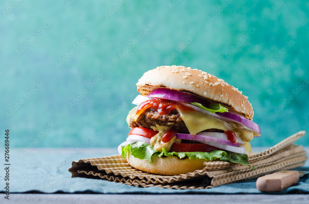 Fototapeta Traditional burgers with cutlet, fresh vegetables, crispy bun with sesame seeds on a grey wooden  table.