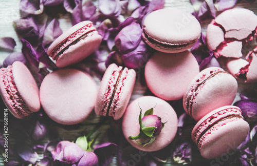 Poster Macarons Sweet pink macaron cookies and lilac rose buds and petals over wooden background, top view, selective focus, close-up. Food texture, background and wallpaper